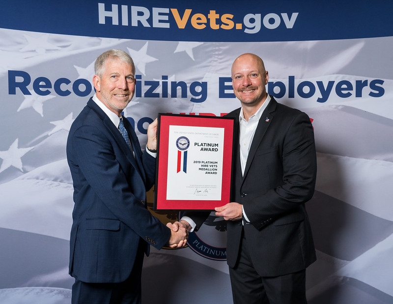 Matthew Herring, Knight Federal's VP Business Development accepts HIRE Vets Platinum Medallion Award from Deputy Assistant Secretary for Operations, Sam Shellenberger at the HIRE Vets Awards.